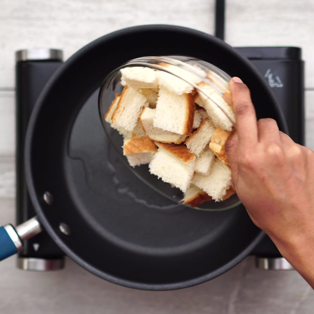 Adding bread pieces into a pan with oil