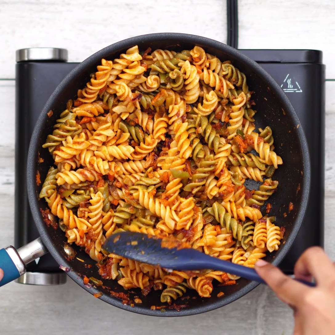 Adding cooked pasta and coating evenly