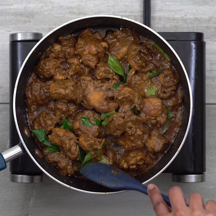 Adding curry leaves into the chicken and mixing