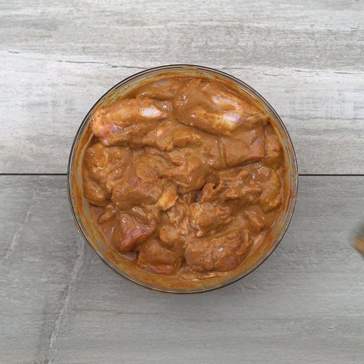 Mixing masala and chicken well