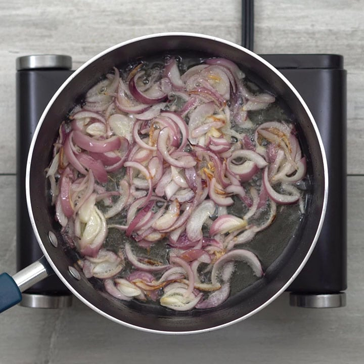 Adding oil and onion and sautéing well
