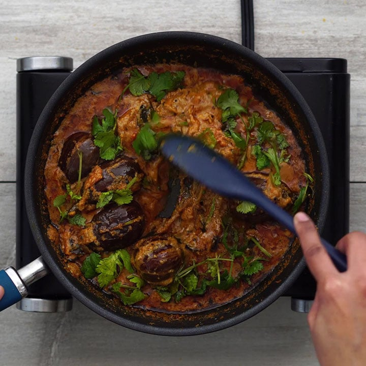 Garnishing the curry with coriander leaves