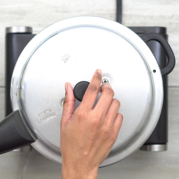 Closing the pressure cooker and boiling dal