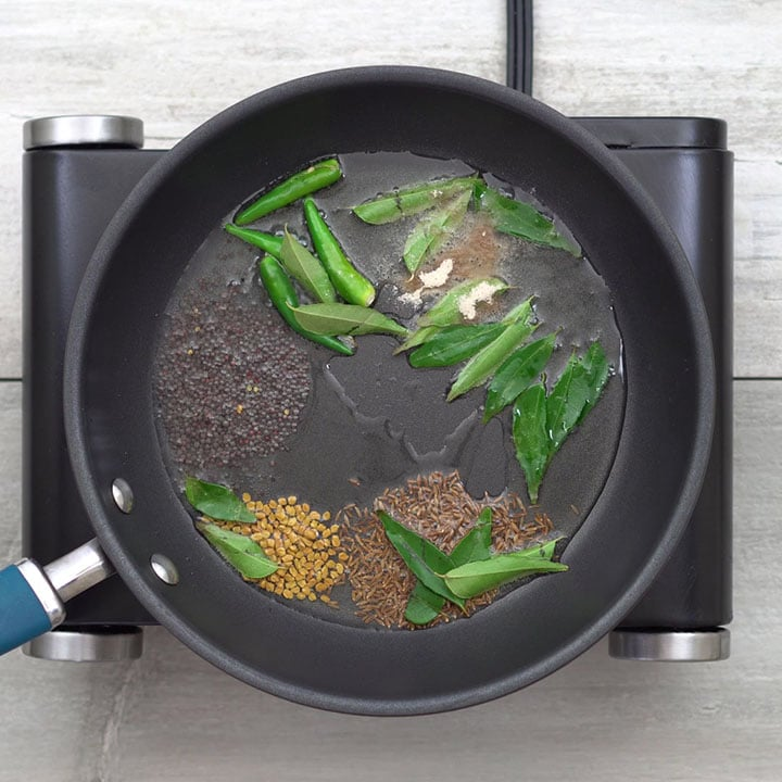 Adding Indian spices and allowing it to splutter