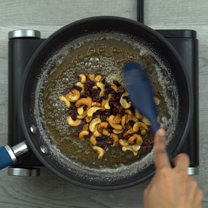 mixing fried nuts and cardamom powder