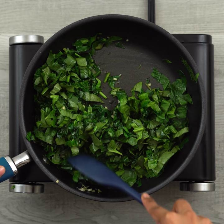 Stirring spinach until it is wilted