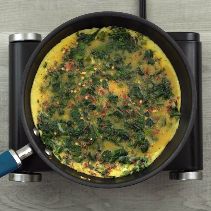 cooking of Spinach omelette mixture in a pan