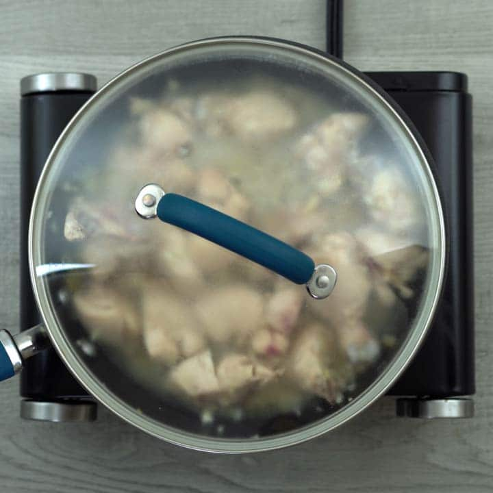 chicken cooking in the pan with lid closed