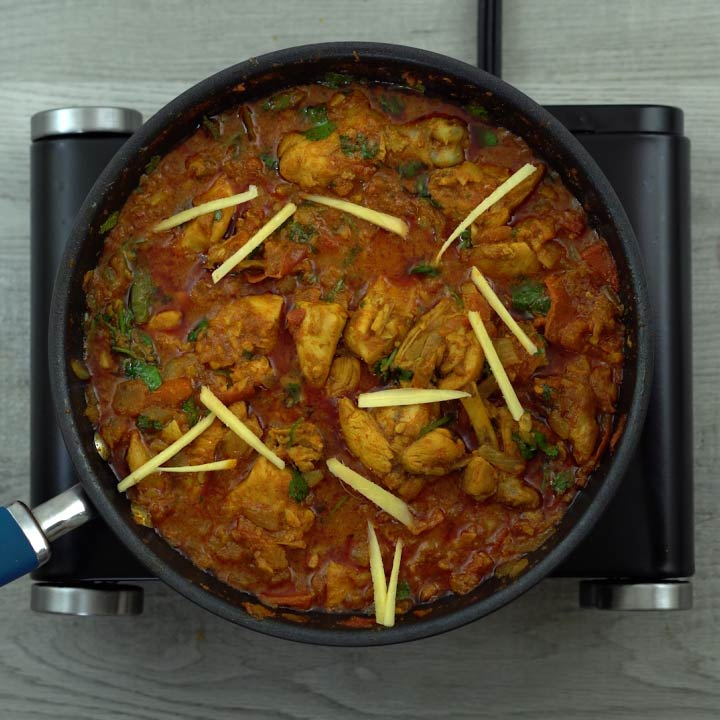 chicken karahi garnished with ginger and coriander leaves