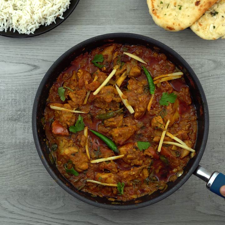 serving chicken karahi or kadai chicken with naan and rice