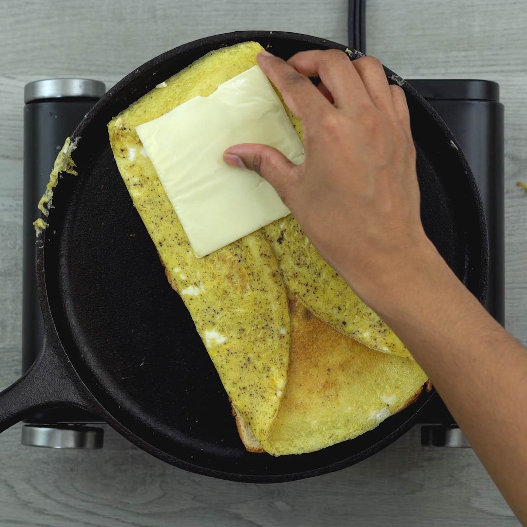placing cheese on the bread omelet