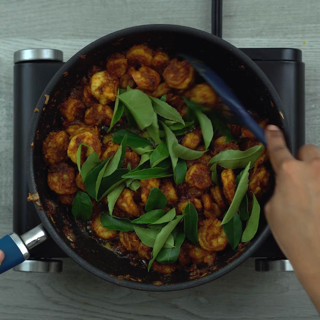 adding curry leaves to the prawn