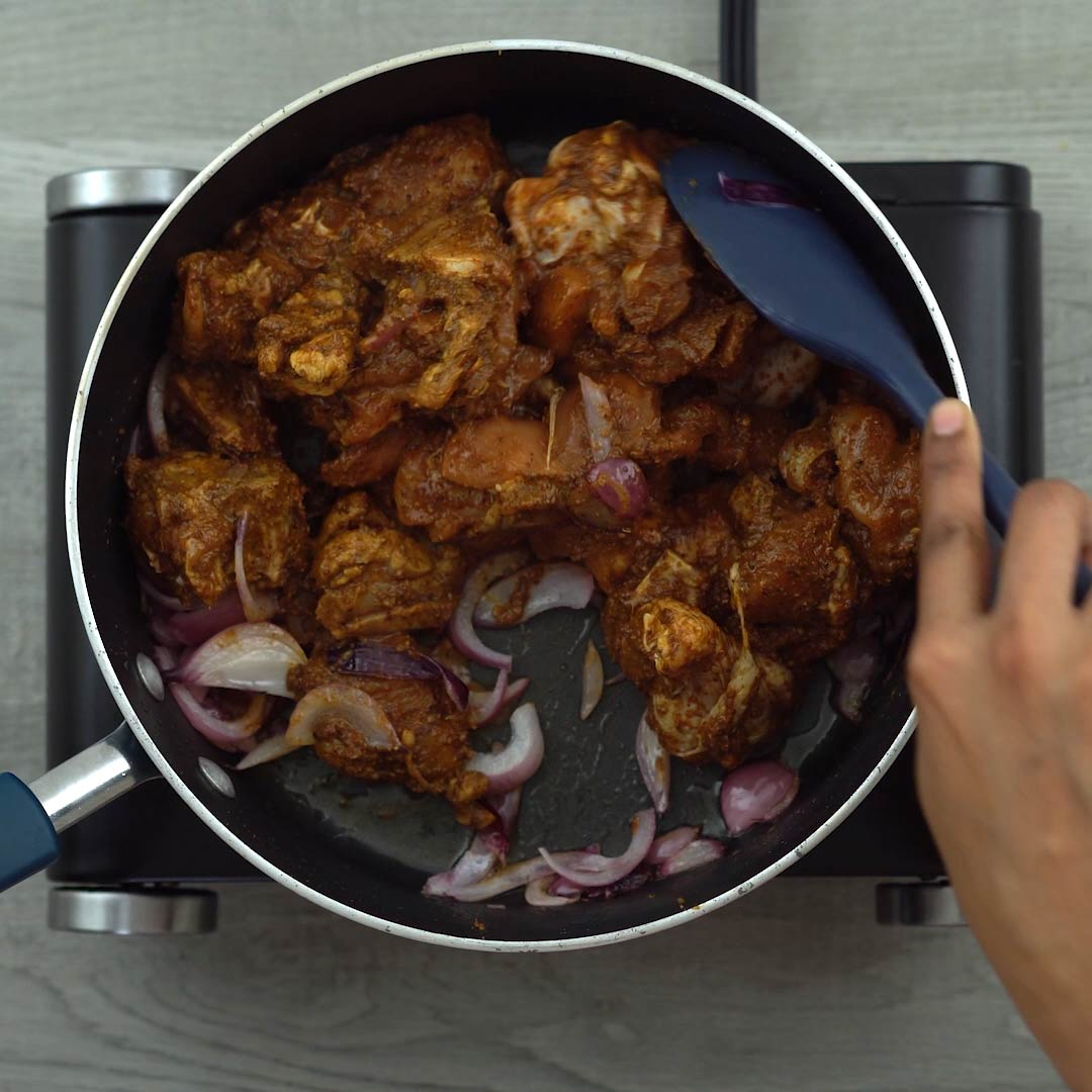 Sautéing marinated chicken with onions