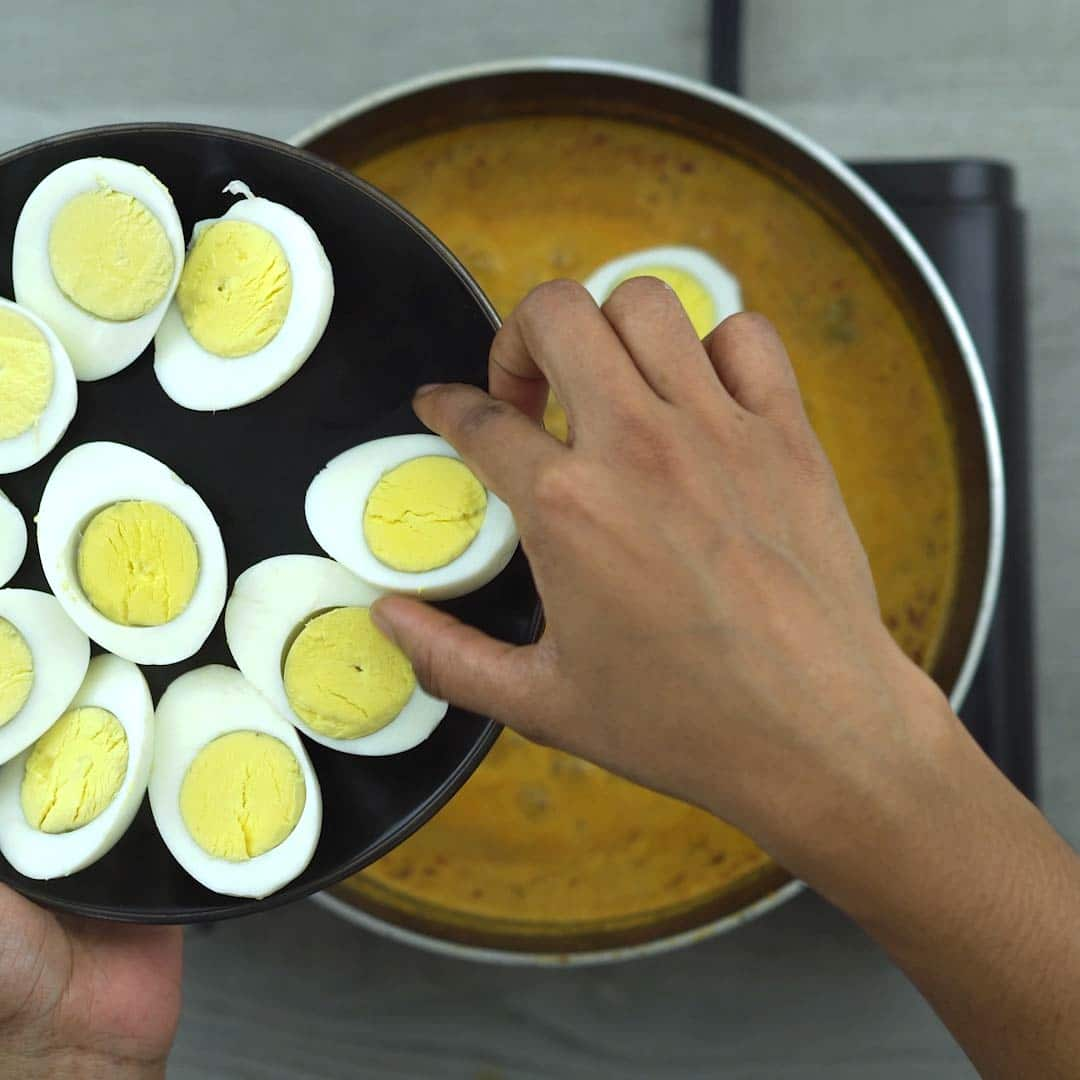 adding boiled eggs to the curry