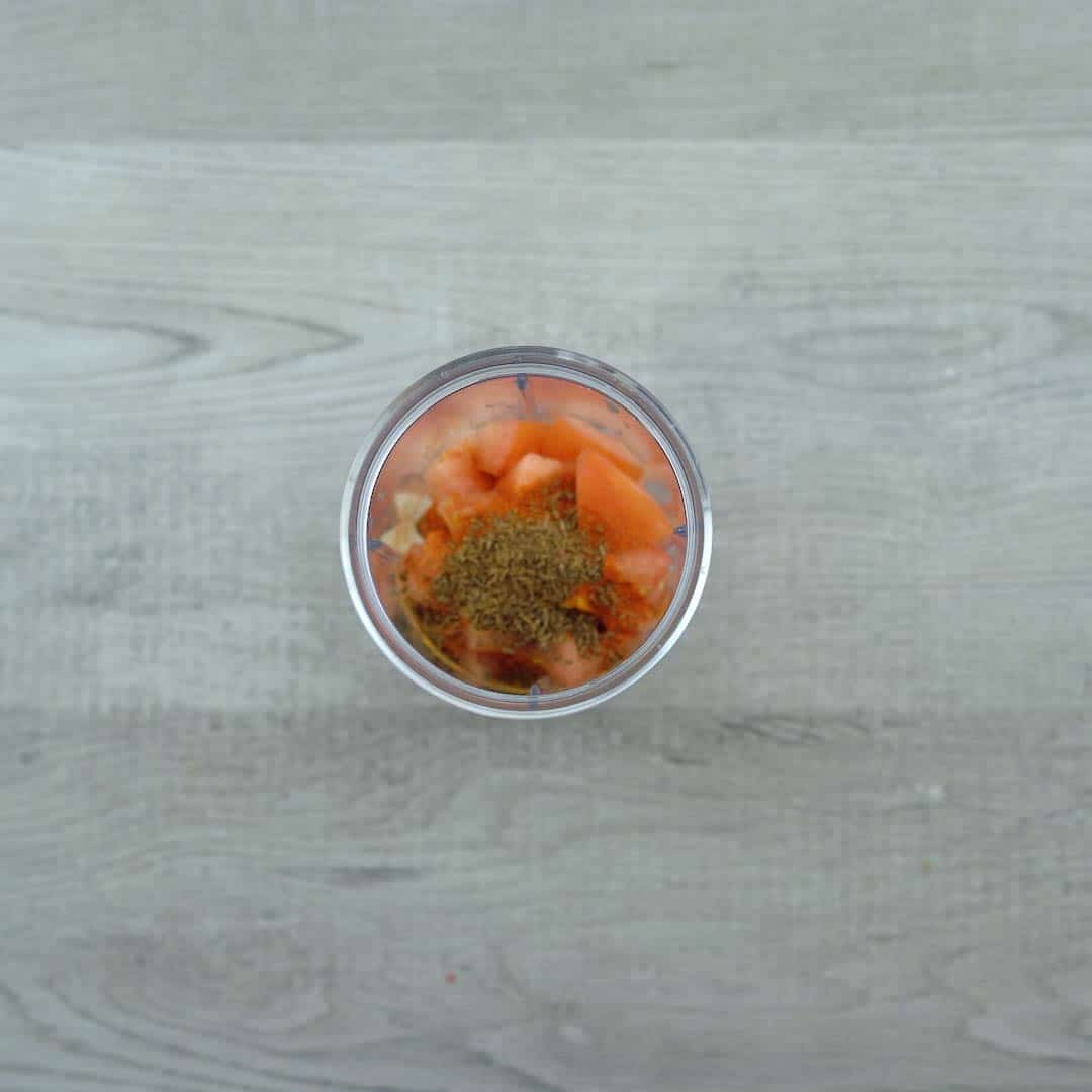 onion, tomatoes and spice powders in a blender
