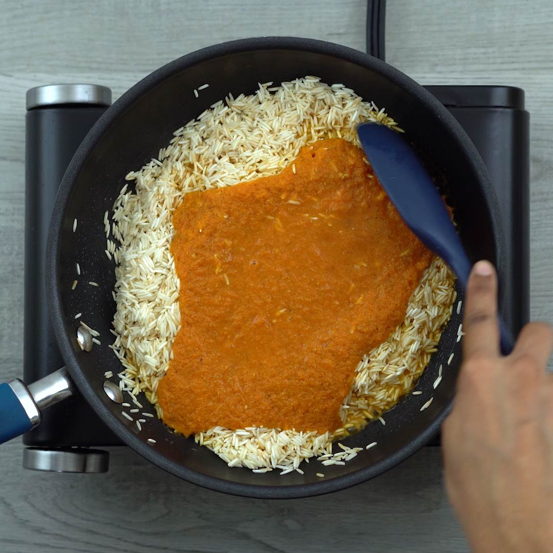 Mixing tomato spice mix to rice