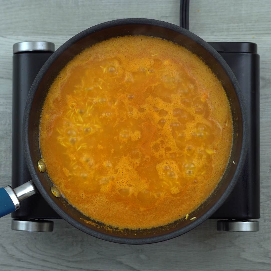 rice is cooking in tomato water mixture