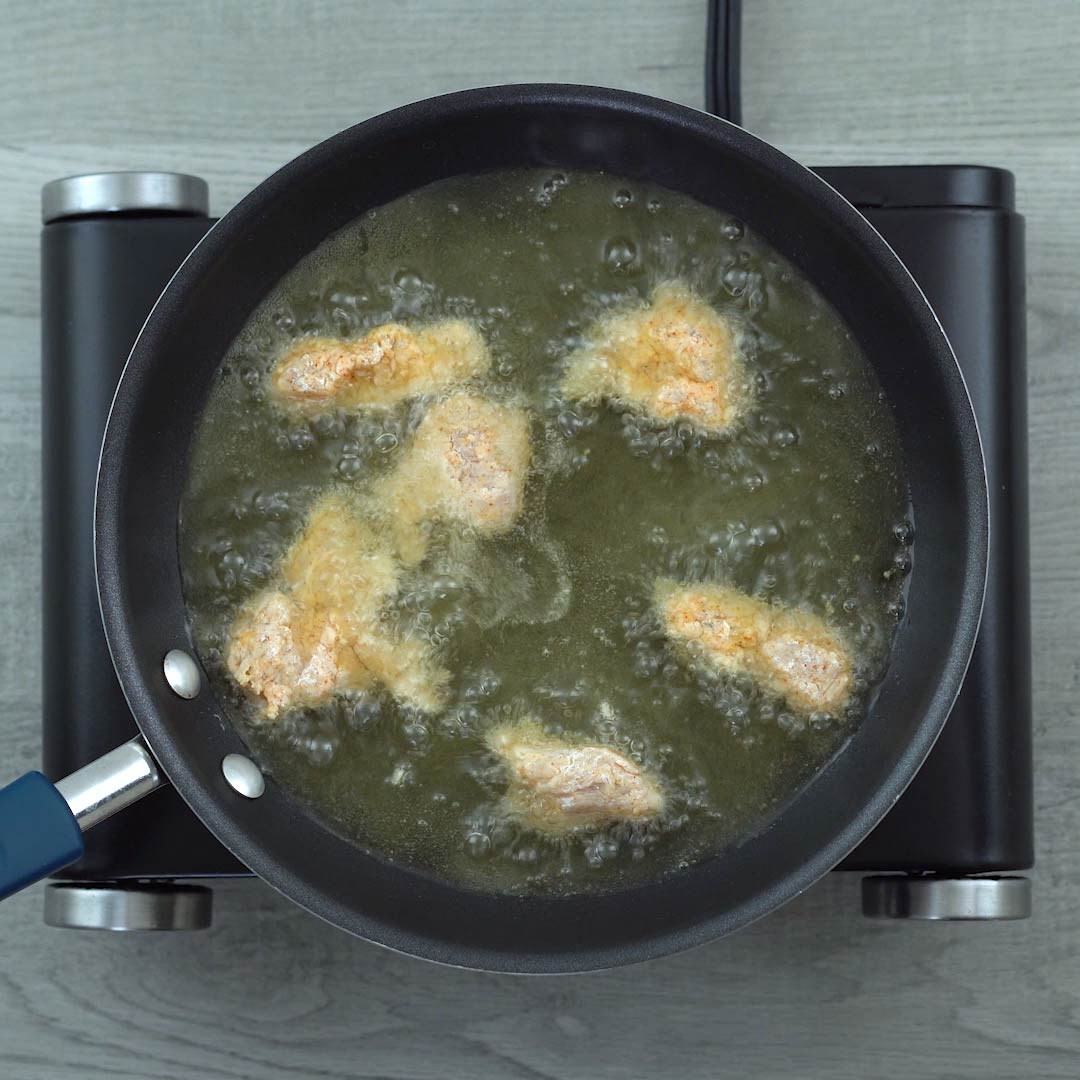 frying the flour coated chicken in oil