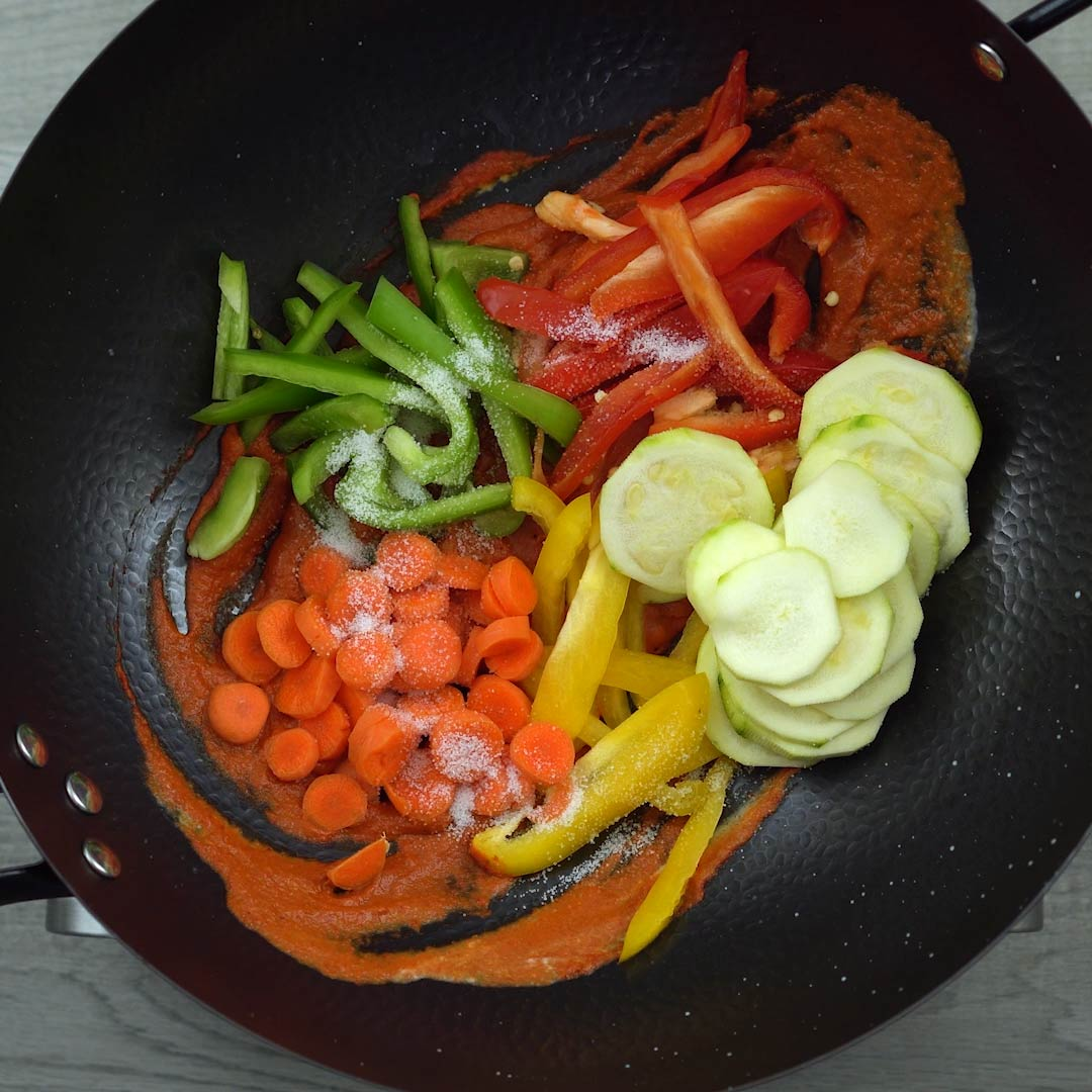 vegetables and salt added to the wok