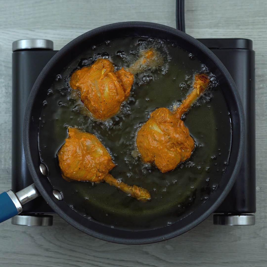 marinated chicken pieces are frying in oil
