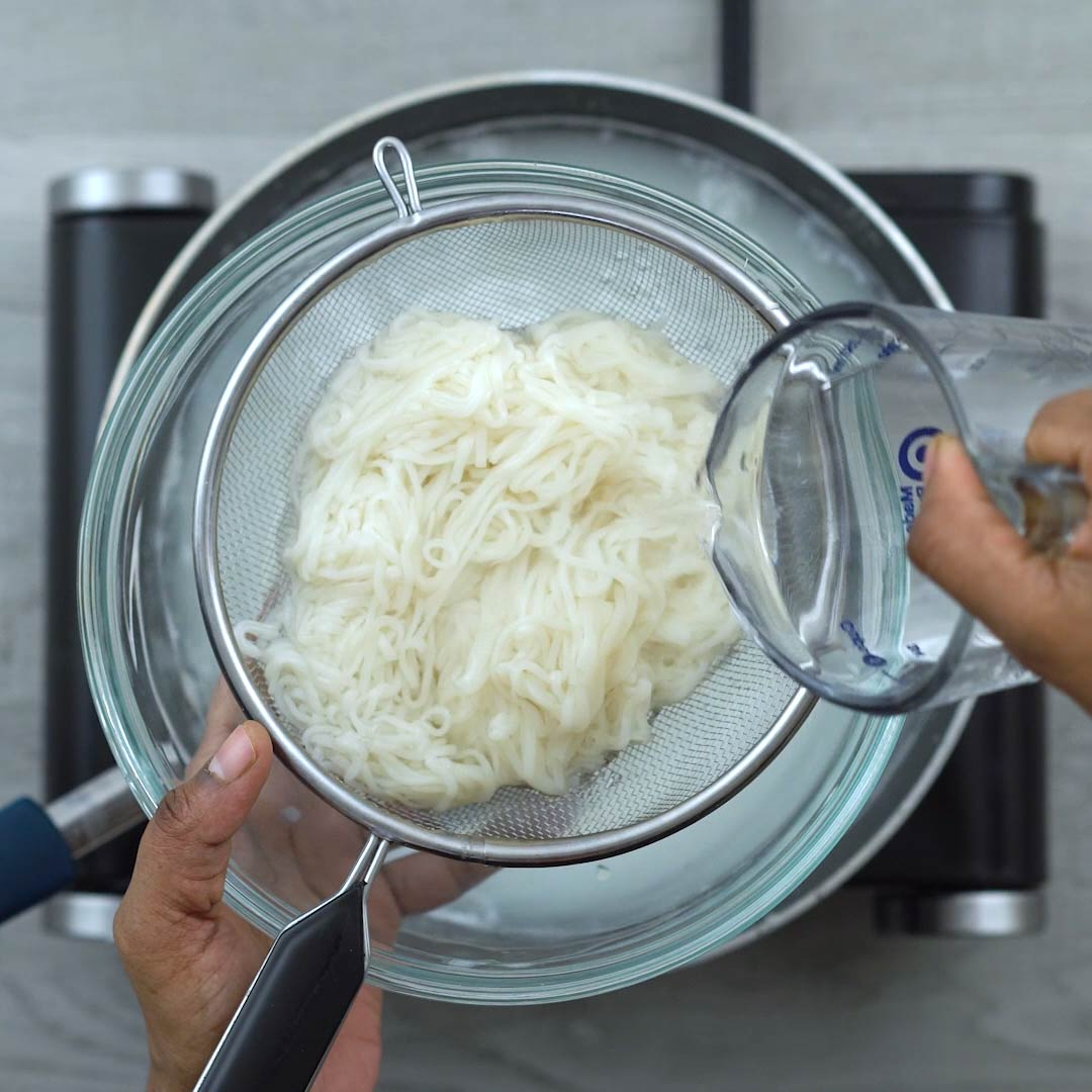 pouring water over cooked rice noodles