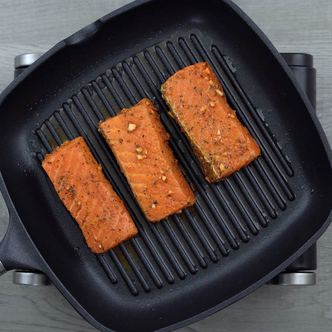 salmon is cooking in grilling pan